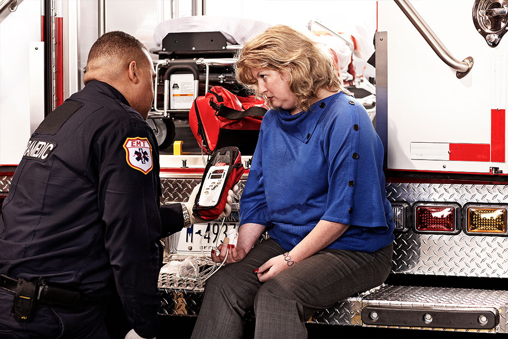 Masimo - EMT using Rad-57 on woman sitting on back of ambulance